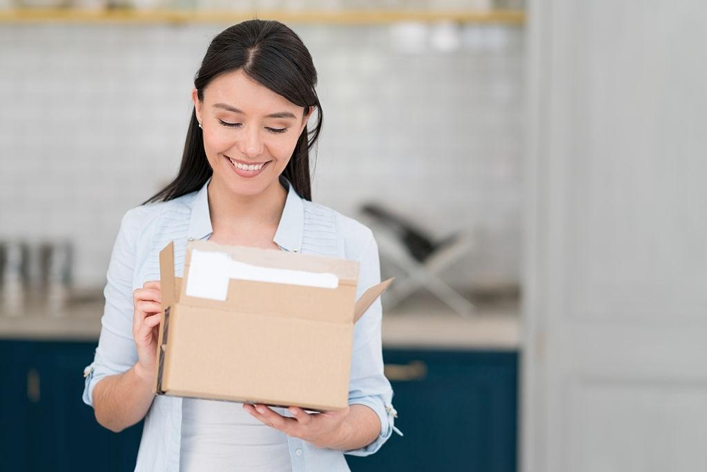 a female happily open a parcel box
